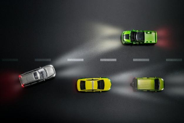 Hoogste mening van het model van autospeelgoed op de weg bij nacht met achteloos drijvend concept.