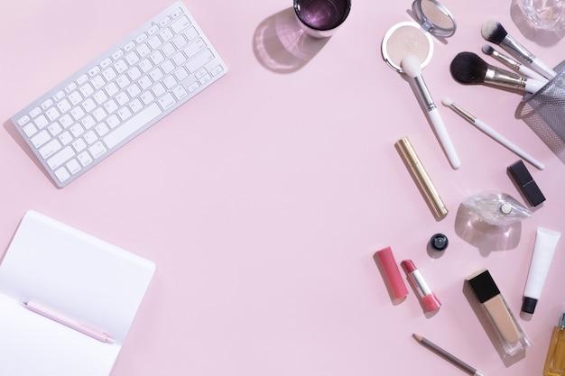 Hoogste mening van het werkende bureau van de vrouwenschoonheid blog met computer of laptop, notitieboekje, decoratief schoonheidsmiddel, bladerenschaduwen en hard licht, envelop op roze en witte pastelkleurlijst. plat lag achtergrond.