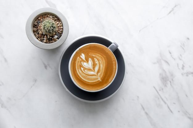 Hoogste mening van hete cappuccino in koffiekop op marmeren lijst