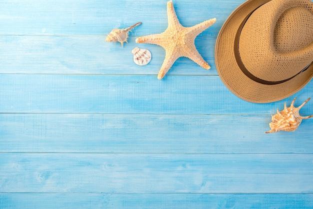 Hoogste mening van hoed en overzeese shell op lichtblauwe houten plankvloer voor de zomervakantiestijdrug