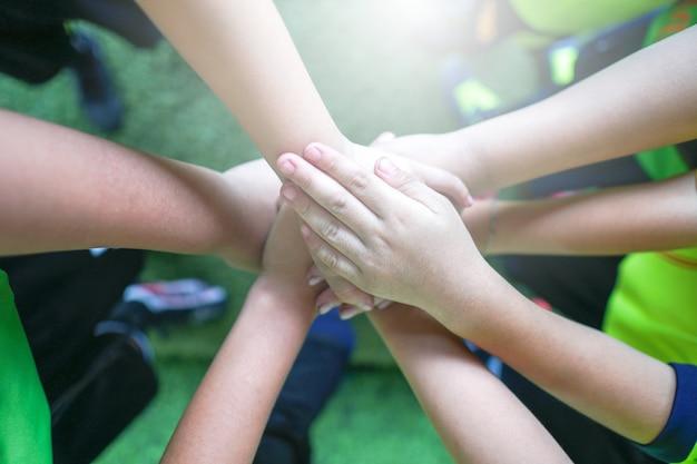 Hoogste mening van hoog vijf gebaar van de jonge geitjeshand in ondergeschikt voetbalteam