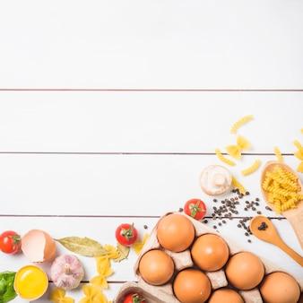 Hoogste mening van ingrediënten voor het koken van deegwaren op witte houten lijst