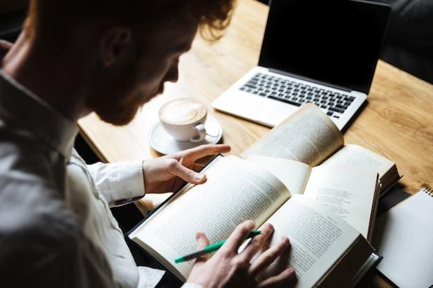 Hoogste mening van jonge roodharige mannelijke student die voor universitair examen voorbereidingen treft