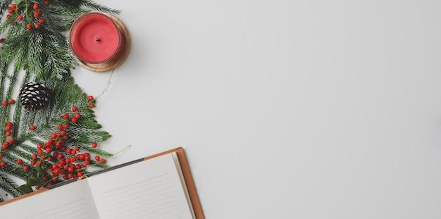 Hoogste mening van kerstmiswerkruimte met exemplaarruimte en kerstmisdecoratie met open notitieboekje op wit bureau