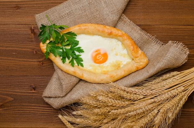 Hoogste mening van khachapuri met ei op jute en houten lijst