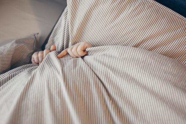 Hoogste mening van klein jong geitje in bed die zijn gezicht behandelen met deken. ochtend