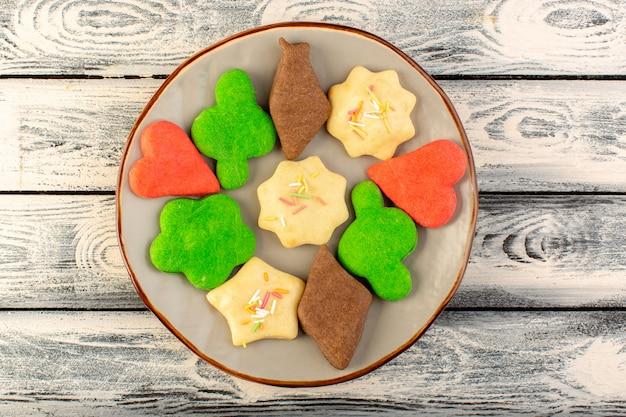 Hoogste mening van kleurrijke heerlijke verschillende koekjes gevormd binnen ronde plaat op het grijze houten bureau