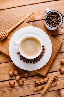 Hoogste mening van koffiekop die met koffiebonen wordt verfraaid die op houten dienende raad worden geplaatst