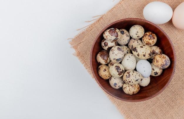 Hoogste mening van kwartelseieren op een houten kom op zakdoek met kippeneieren op witte achtergrond