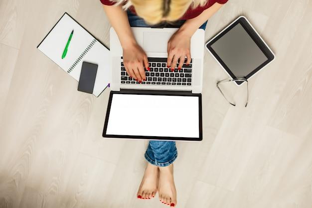 Hoogste mening van laptop in de handen van het meisje die op een houten vloer met koffie zitten