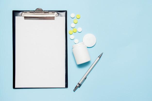 Hoogste mening van leeg document voor het schrijven van artsenvoorschrift. pillen op blauw