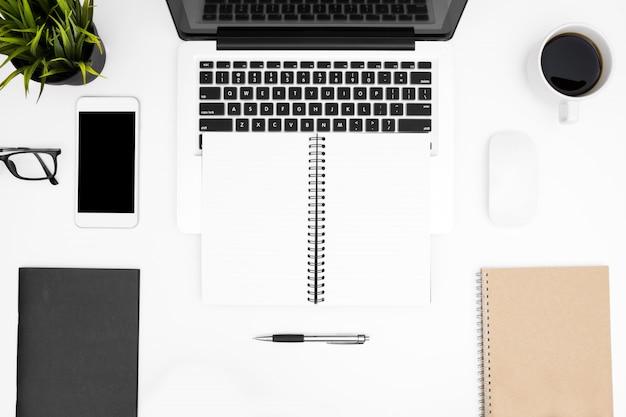 Hoogste mening van leeg notitieboekje met laptop en levering op witte bureaulijst.