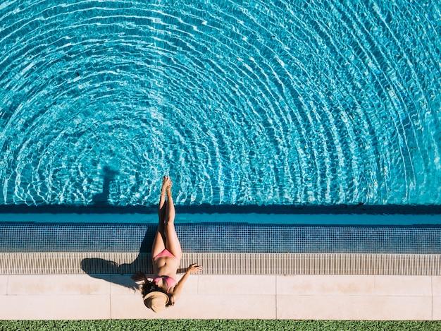 Hoogste mening van meisje het ontspannen naast pool