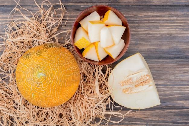 Hoogste mening van meloenplakken in kom en snijd meloen met gehele op stro op houten achtergrond