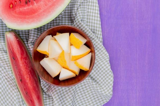 Hoogste mening van meloenplakken in kom met halve watermeloen en plak op purpere achtergrond met exemplaarruimte