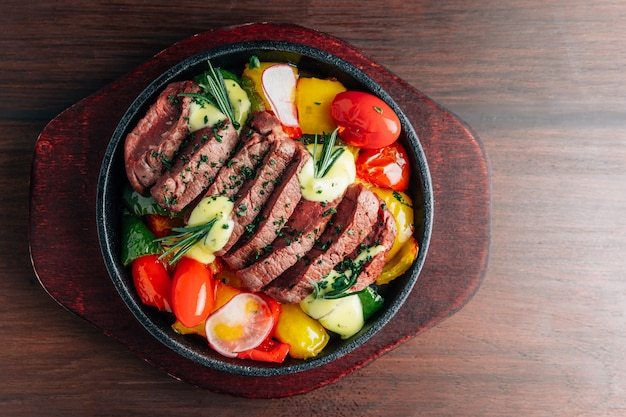 Hoogste mening van middelgroot zeldzaam die rundvleeslapje vlees in warmhoudplaat met tomaat, groene paprika, radijs en rozemarijn wordt gediend.