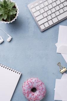 Hoogste mening van notitieboekje en doughnut op bureau
