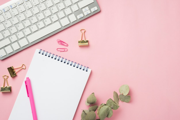 Hoogste mening van notitieboekje en toetsenbord op bureau met droge bladeren