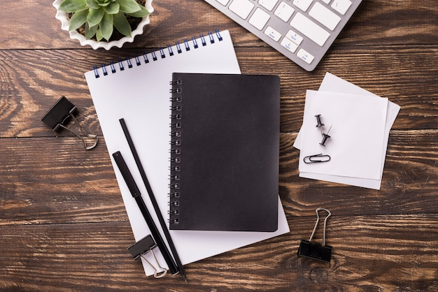 Hoogste mening van notitieboekje en toetsenbord op houten bureau met succulent