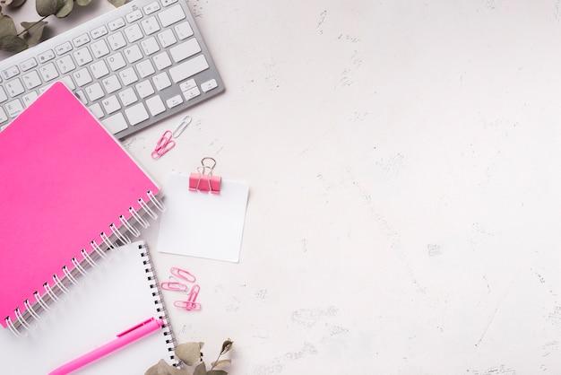 Hoogste mening van notitieboekjes op bureau met toetsenbord en exemplaarruimte