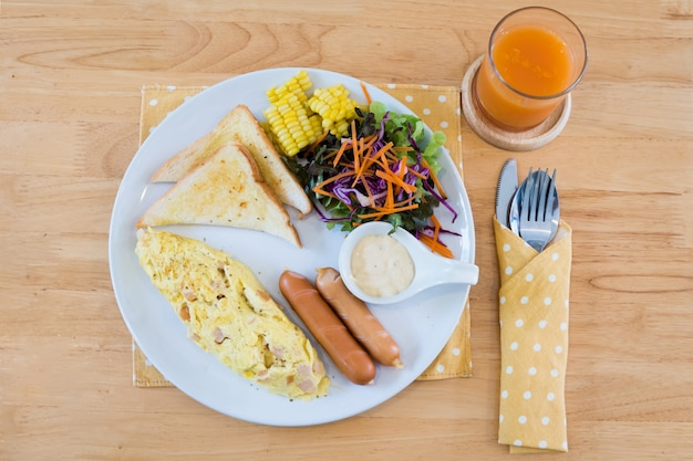 Hoogste mening van omelet met hotdog, croissants, graangewassen en vruchten op houten lijst. gebalanceerd dieet.