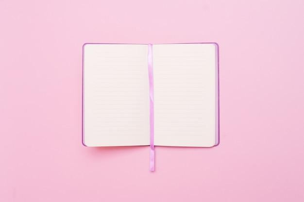 Hoogste mening van open leeg notitieboekje op pastelkleur roze kleurrijke achtergrond