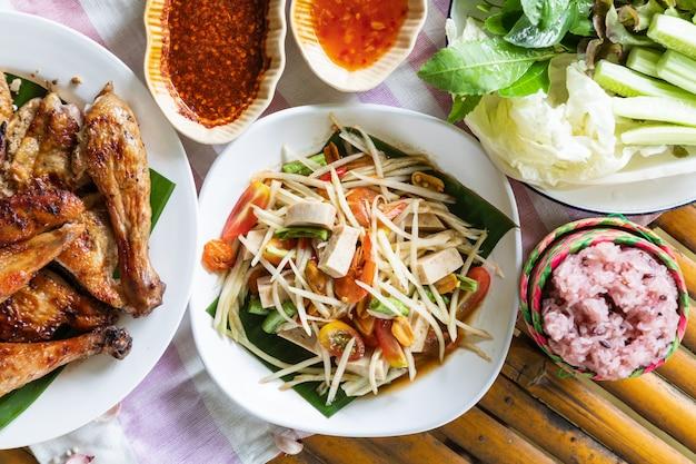 Hoogste mening van papajasalade en geroosterde kip in witte plaat op bamboeachtergrond