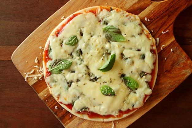 Hoogste mening van pizza met halloumi-kaas, tomatensaus en basilicum dat op houten plaat wordt gediend