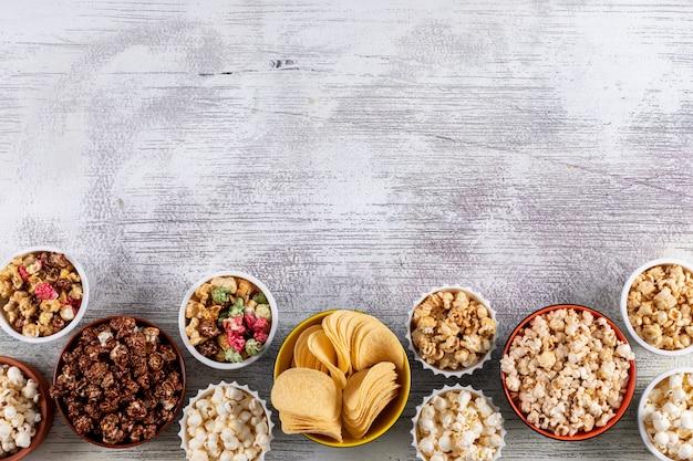 Hoogste mening van popcorn en spaanders in kommen met exemplaarruimte op witte houten horizontaal