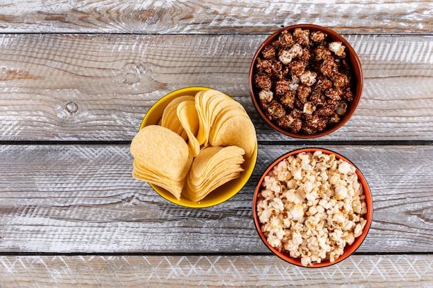 Hoogste mening van popcorn en spaanders in kommen op witte houten horizontaal