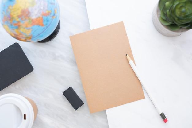 Hoogste mening van potlood op papier met blauwe bol, bord, marmeren lijst van de koffiekop