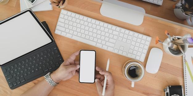 Hoogste mening van professionele ontwerper die idee op smartphone op houten lijst zoeken