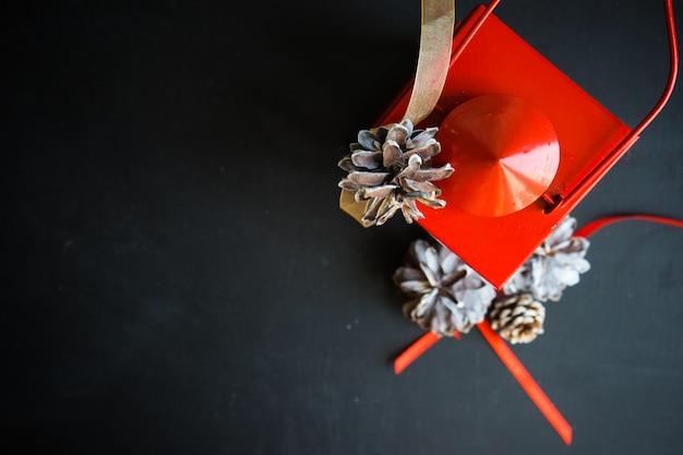 Hoogste mening van rode kaarshouder en denneappels op donkere achtergrond als kerstmisconcept