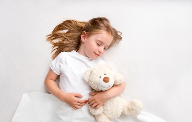 Hoogste mening van slaperig meisje die teddybeer koesteren die op wit bed leggen