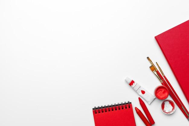Hoogste mening van slordig wit bureau met leeg notitieboekje op witte achtergrond