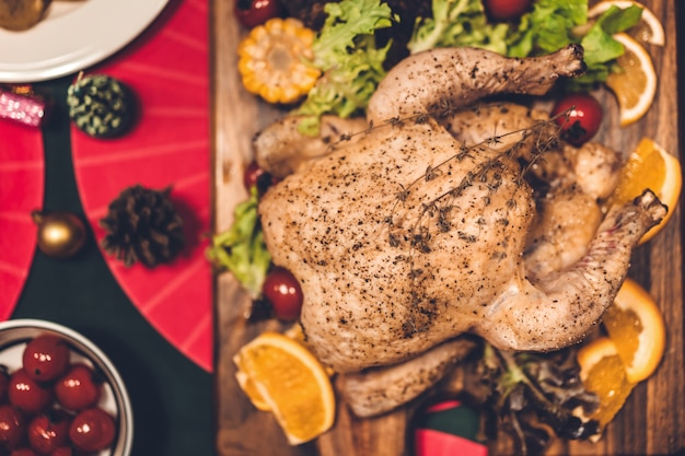 Hoogste mening van smakelijke gebakken geroosterde gehele gebraden kip en salade met kerstmisdecoratie op de kerstmis themed dinerlijst
