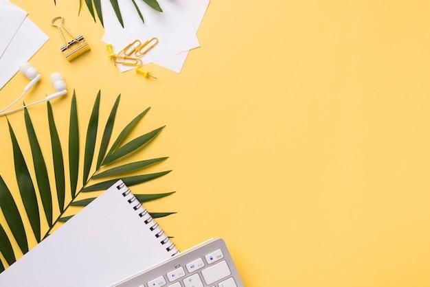 Hoogste mening van toetsenbord op bureau met notitieboekje en exemplaarruimte