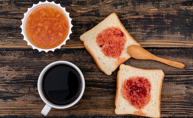 Hoogste mening van toosts met jam en koffie op donkere houten horizontale oppervlakte