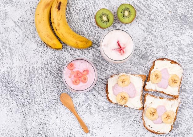Hoogste mening van toosts met yoghurt en vruchten op witte horizontale oppervlakte