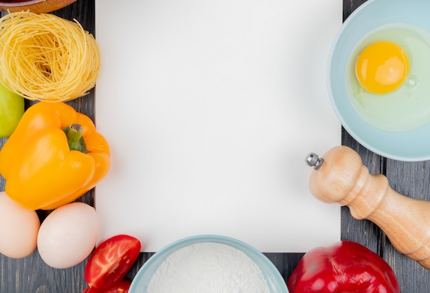 Hoogste mening van vers eigeel en wit op een kom met zoute schudbeker met een oranje groene paprika op een houten achtergrond met exemplaarruimte