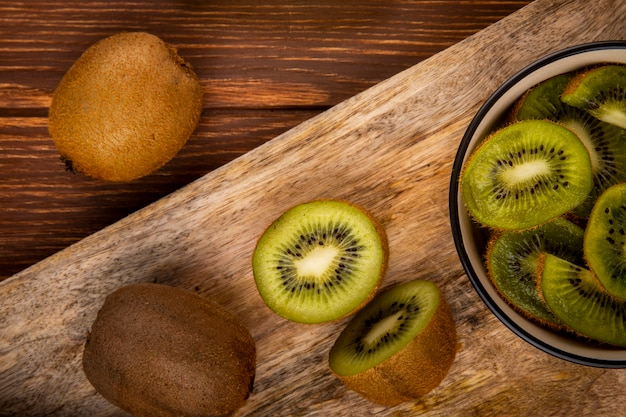 Hoogste mening van vers kiwifruit en plakken van kiwi op een houten scherpe raad op plattelander
