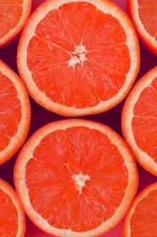 Hoogste mening van verscheidene grapefruitplakken op heldere achtergrond in roze kleur