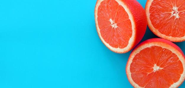 Hoogste mening van verscheidene verscheidene grapefruitplakken op heldere achtergrond in blauwe kleur