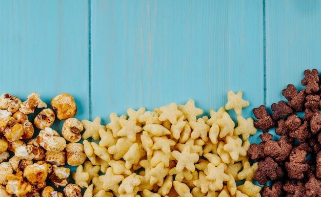 Hoogste mening van verscheidenheid van ontbijtcornflakes en graangewassen onderaan met exemplaarruimte op blauwe houten achtergrond