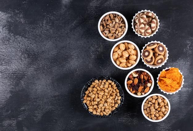 Hoogste mening van verschillend soort snacks als noten, crackers en koekjes in kommen met horizontale exemplaarruimte op donkere horizontale achtergrond