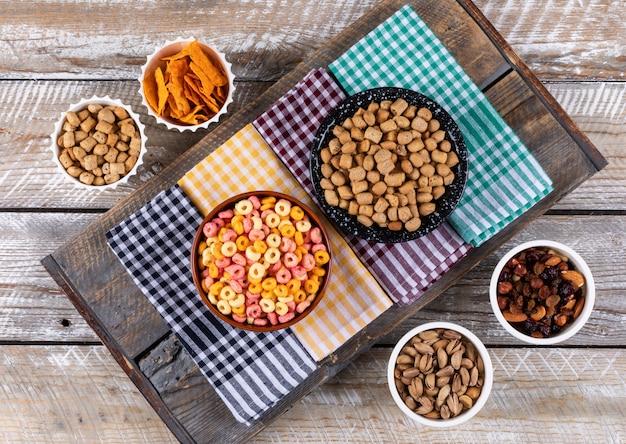 Hoogste mening van verschillend soort snacks als noten, crackers en koekjes op servetten op witte houten horizontale oppervlakte