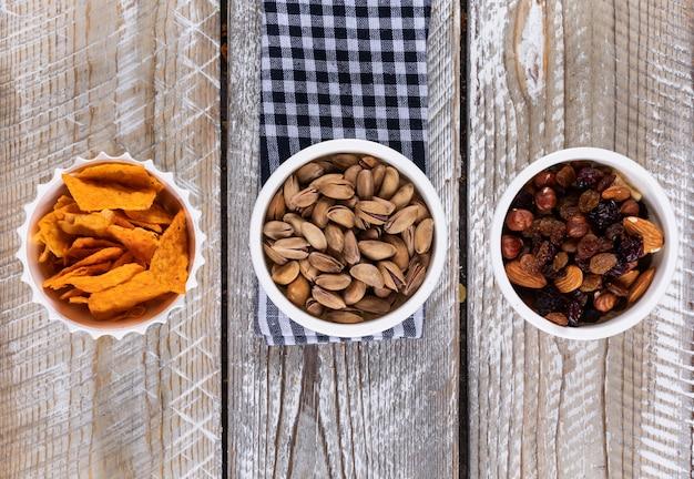 Hoogste mening van verschillend soort snacks als noten en spaanders op servet op witte houten horizontale oppervlakte