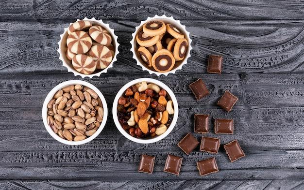 Hoogste mening van verschillend soort snacks zoals noten, koekjes en chocolade in kommen op donkere horizontale oppervlakte