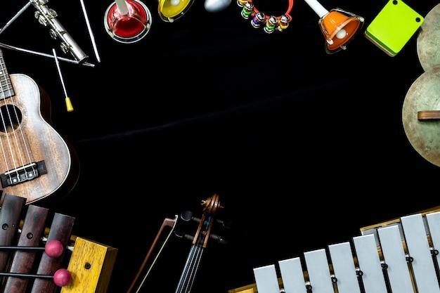 Hoogste mening van vioolgitaar en ukelele met slaginstrumenten op de zwarte achtergrond