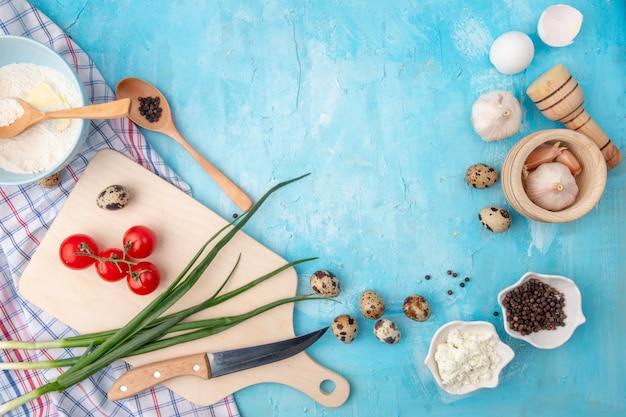 Hoogste mening van voedsel als het eiknoflook van de tomaten lente-ui en anderen met mes en scherpe raad op blauwe achtergrond met exemplaarruimte